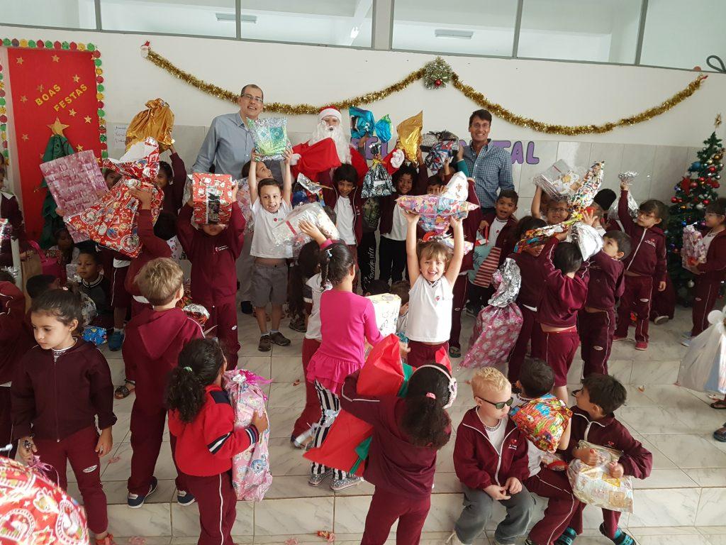 Crianças felizes segurando presentes no natal